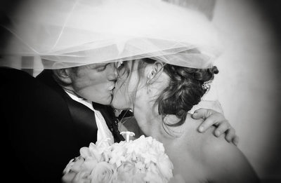 Bride Leans in to Kiss the Groom Caught Under Her Veil