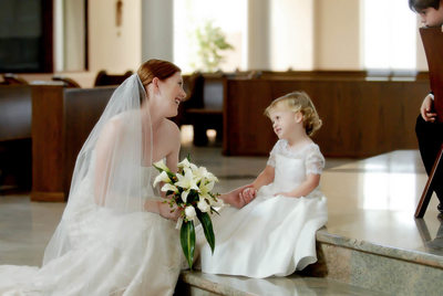 Bride smiles at flower girl