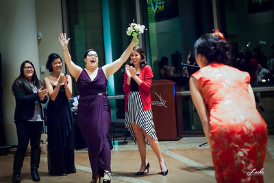 Woman throws hands in air to celebrate catching the bouquet at the reception.