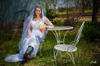 Country Bride Sits Outside in Her Wedding Dress and Boots