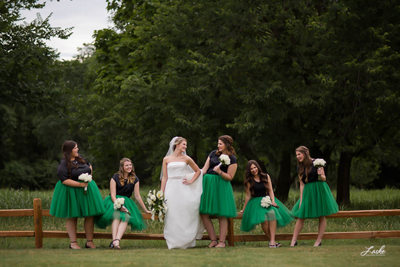 Bride Smiles at her Bridesmaids as they Stand Outside By Wooden Fence