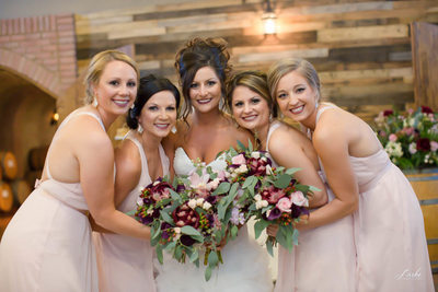 Bridesmaids Lean in Around Bride in Wedding Party Portriat