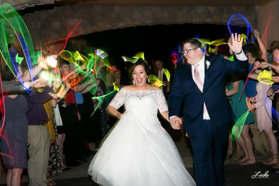 Bride and Groom Run Through Line of Guests After Reception