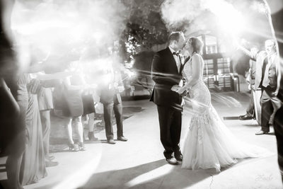 Bride and Groom Stop to Kiss Each Other as Their Wedding Guests Wave Sparklers