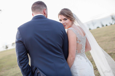 Bride Looks Over Groom's Shoulder as they walk across the field
