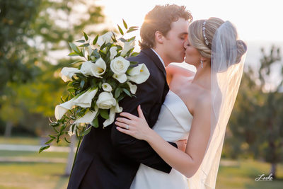 Groom Kisses Bride Holding Bouquet at Dusk