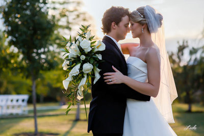 OKC Wedding Photographers Bride and Groom Stand Face to Face at Sunset