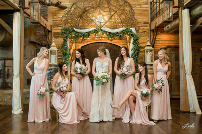Wedding Photographers in Oklahoma City Bride Looks at Bridesmaids as they Pose for a casual wedding day portrait