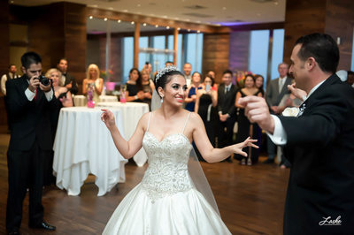 Man takes picture of Bride and Groom Dancing at Wedding Reception