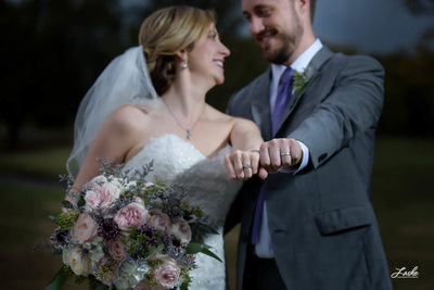Bride and Groom extend arms to show off their wedding rings with fists side by side