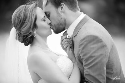 Groom Leans Over to give Bride Kiss