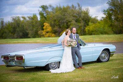 OKC Wedding Photographers Bride and Groom stand by pontiac thunderbird parked on the grass by water