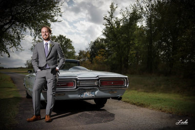 OKC Wedding Photographers Groom Leans on Old Thunderbird in Tux on Wedding Day
