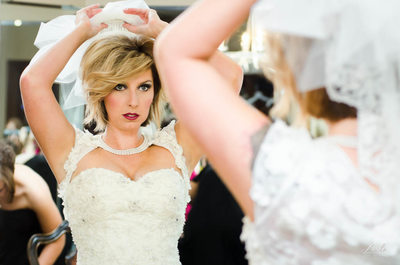 Bride Puts Her Veil on Her Head as She Looks in Mirror