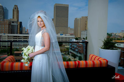 Bride Stands on Balcony of Aloft Hotel With OKC Skyline in Back