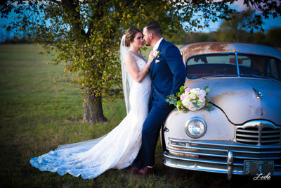 Bride Moves Towards Groom Leaning on Car at Southwind Hills