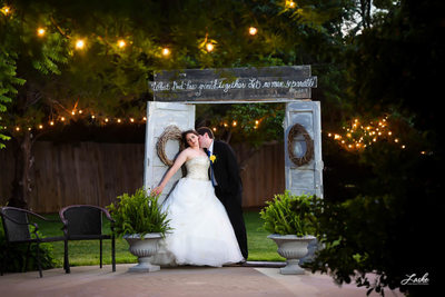 Groom Kisses Bride on Neck in Beautiful Outdoor Setting