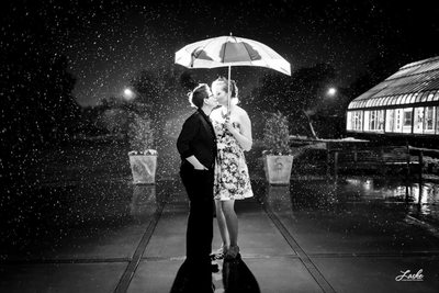 OKC Wedding Photographer Shoots Lesbian Couple Kiss in the Rain outside Atrium at Will Rogers Parkway