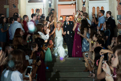 Bride and Groom Laugh As Their Guests Blow Bubbles During their Walk To The Limo