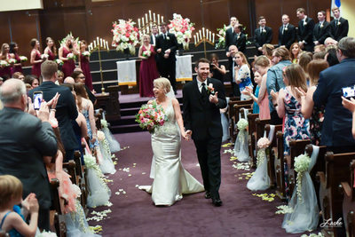 Laughing Couple Walks Down Aisle Leaving Ceremony