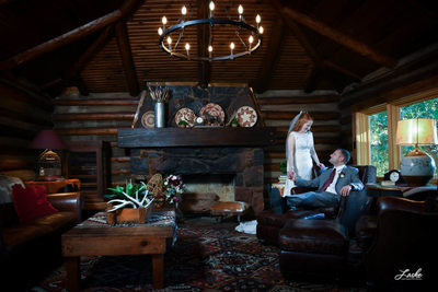 Bride Stands By Her Husband as He Sits on Chair in Lodge