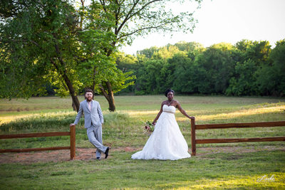 Bride and GRoom each lean against a wood fence post in the middle of the field