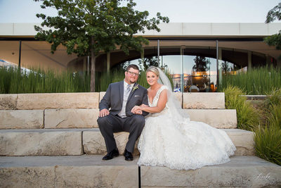 Bride and Groom sit On Stone Wall at Myriad Botanical Gardens