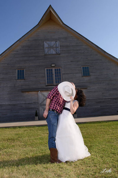 Groom Leans over to kiss bride as she hides them behind his cowboy hat