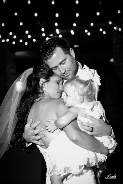 The Groom Embraces His Bride and Daughter as they Dance