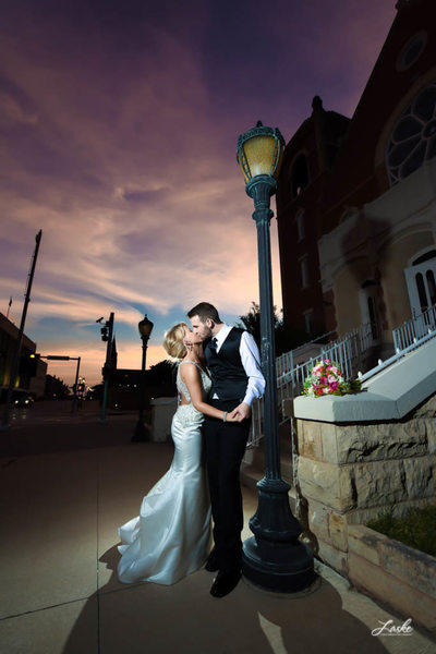 Bride and Groom Kiss Under Lamp Post During Sunset