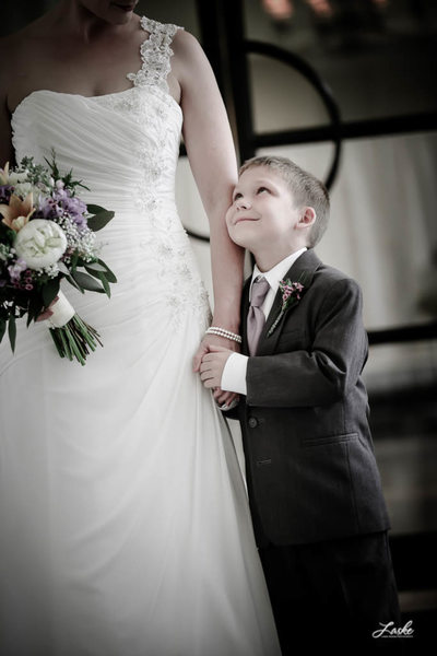 Ring Bearer Gives Warm Smile as he Stands Holding Bride's Hand
