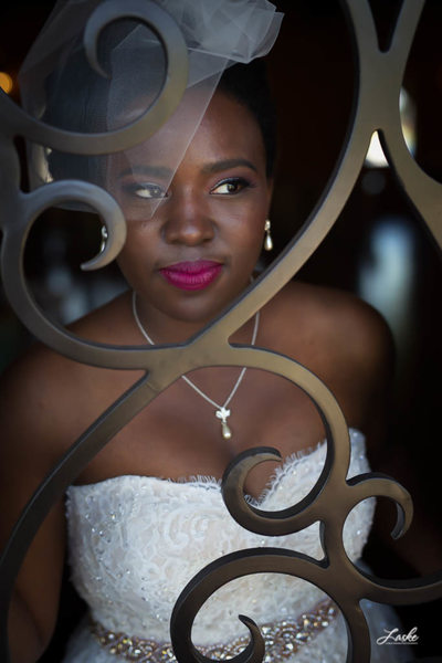 Beautiful Bride Looks Through Curved Iron of Door