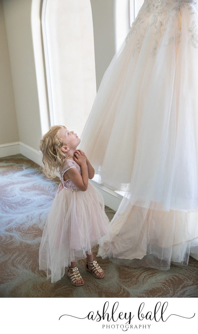 Flower Girl Admiring Bride's Wedding Gown