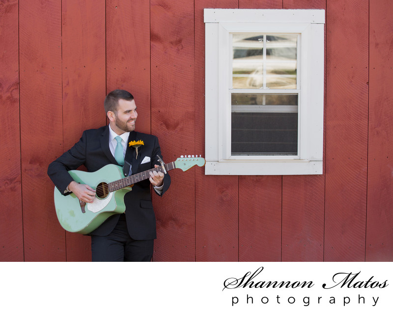 Groom playing guitar at the barn at The Five Bridge Inn