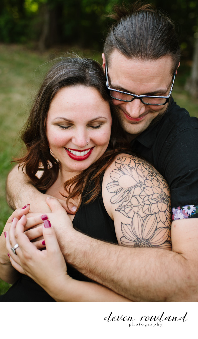 Tattooed Couple Smile and Snuggle in a Natural Pose