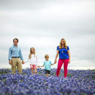 family holding hands in the bluebonnets
