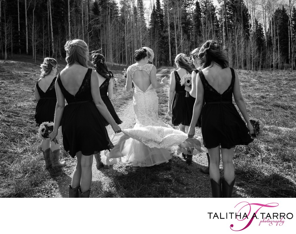 Bridesmaids carrying the dress of the bride as they walk together