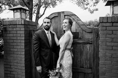 Bride and groom smiling for a picture in front of gate