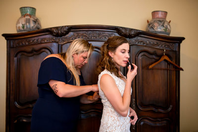 Bride and bridesmaid finishing up the final touches before the wedding