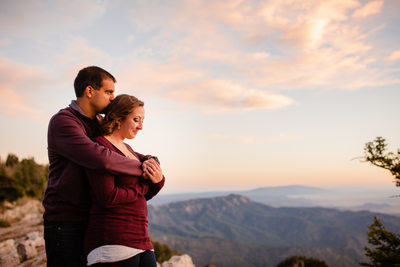 Couple hugging each other at the crest of the mountain