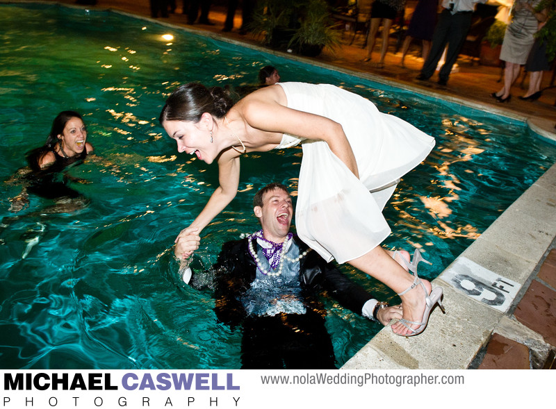 Groom pulls bride into pool