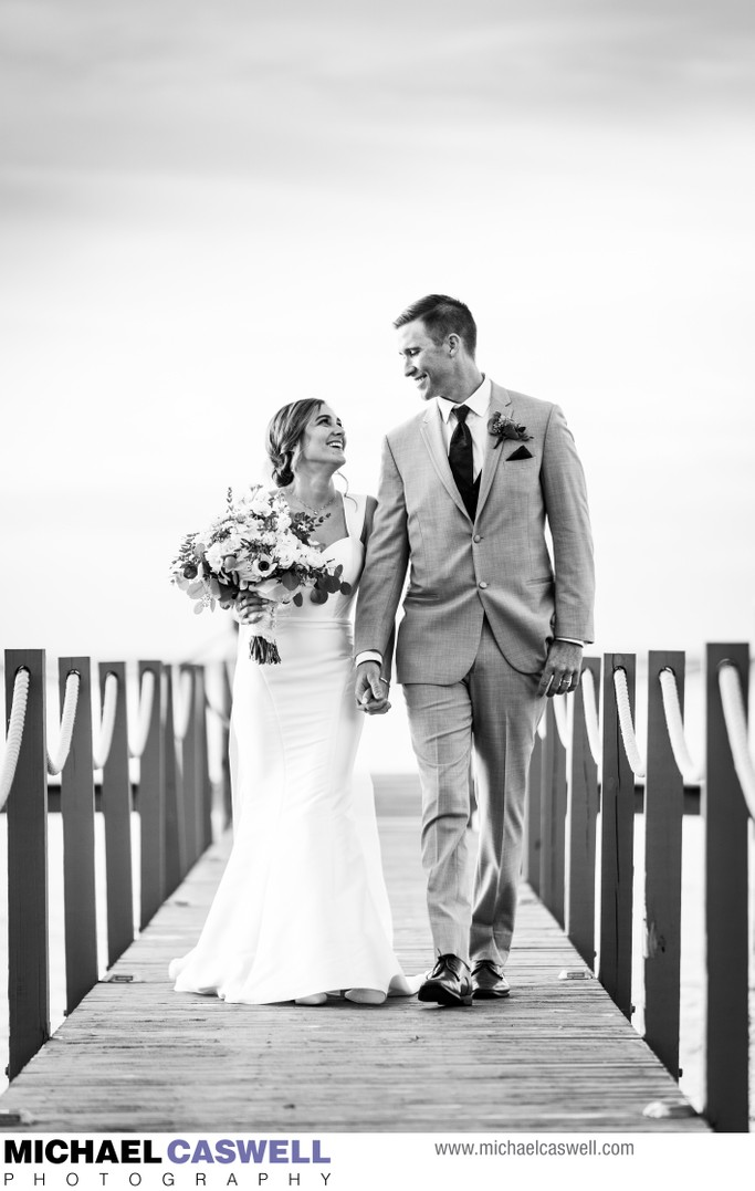 Bride and groom walk along pier