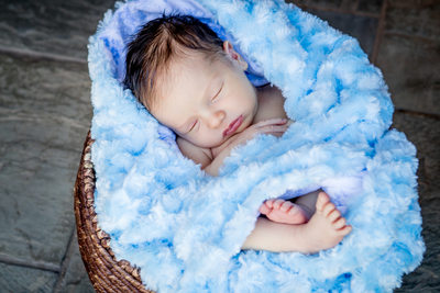 baby boy wrapped in soft cuddly blanket in woven basket