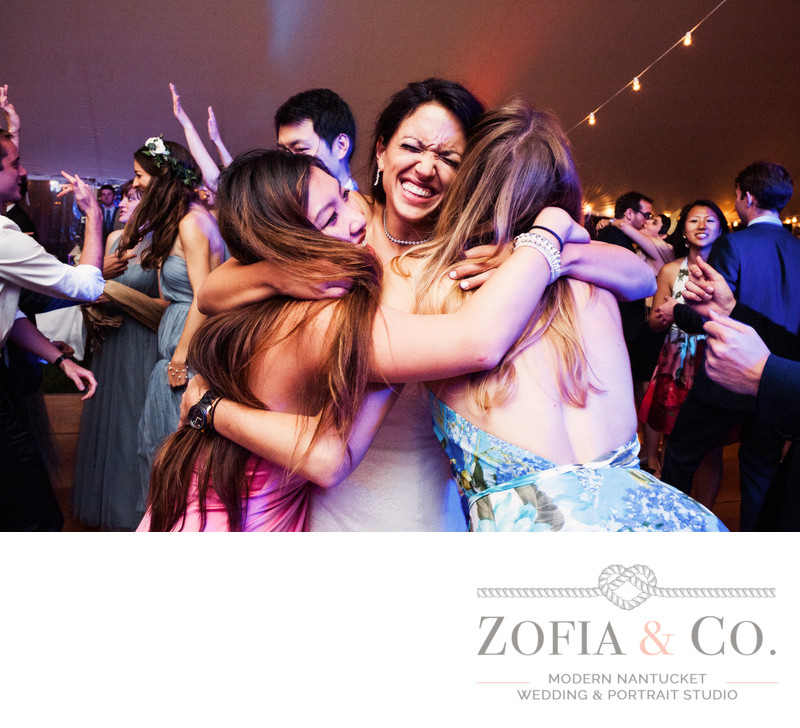 bride hugs friends at tom nevers wedding reception
