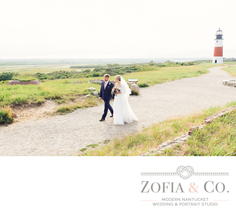 bride and groom walk at sankaty head lighthouse