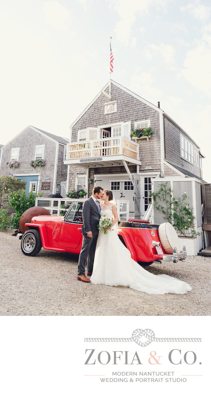 groom and bride kissing in front of red jeepster