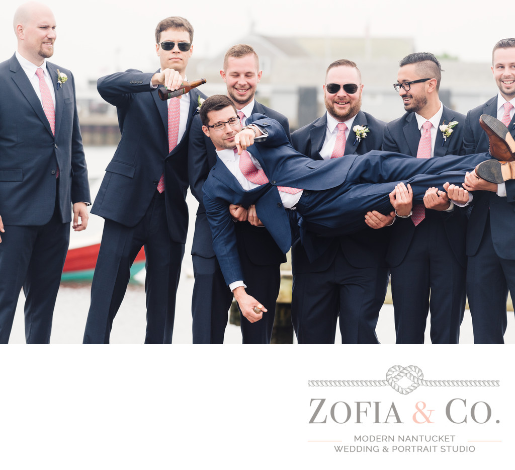 groomsmen in navy suits and pink ties on nantucket harbor