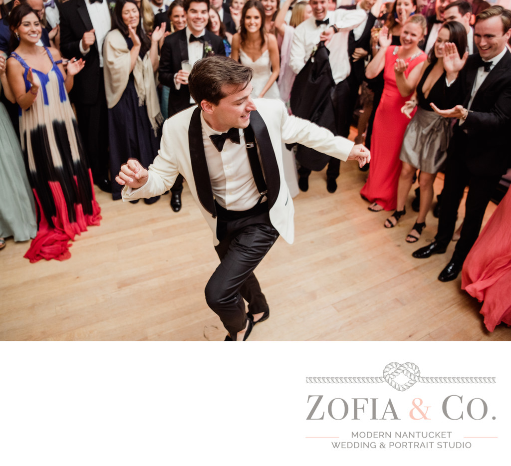 groom in white jacket and black tie dancing
