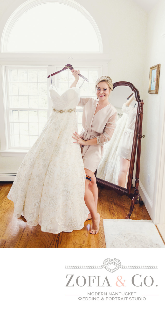 nantucket bride ready to put on her wedding gown at home