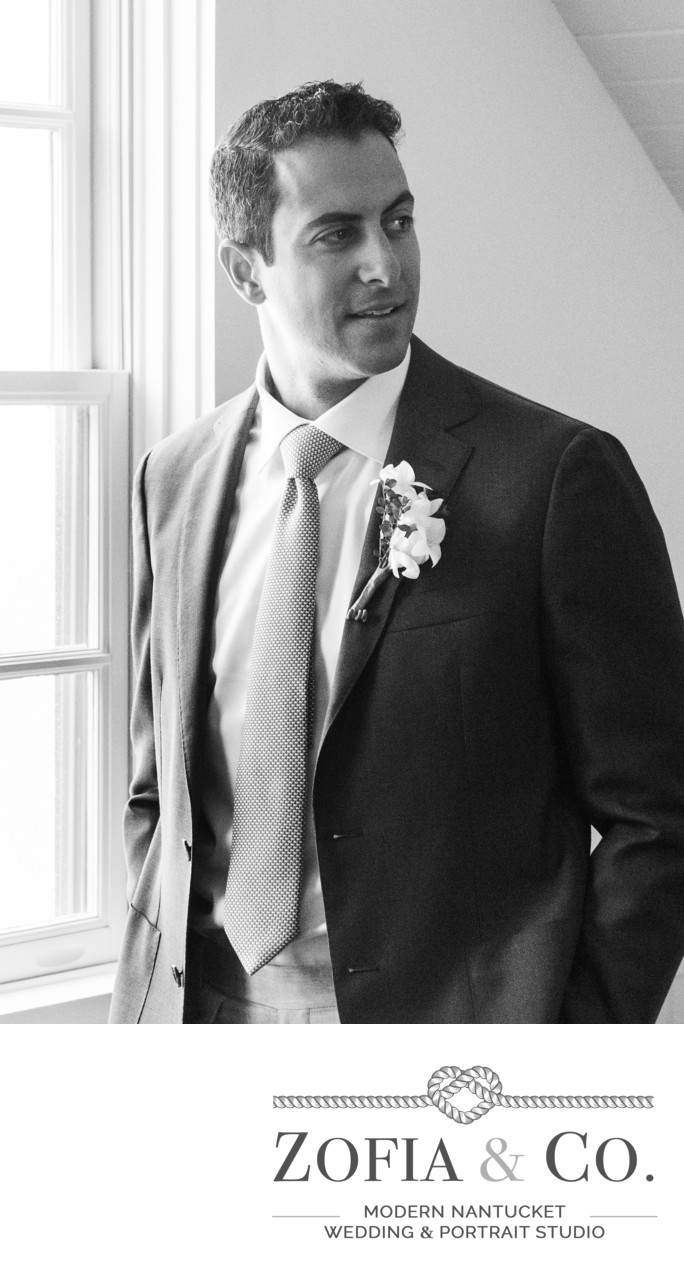 groom in black and white getting ready